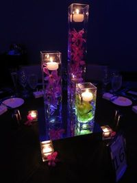 Purple (and Green) Orchids Floating under Candles in Varying Square Vases - A picture perfect centerpiece idea!