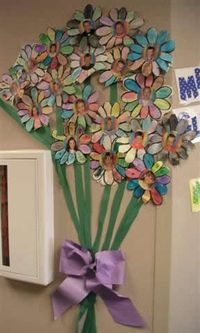 A cute display in the spring outside the classroom door. you could use this for adjectives and have the students write adjectives that describe them self on the petals.