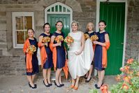 Navy dresses with orange bouquets.