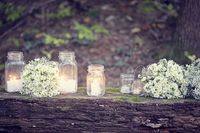 mason jars with candles and white flowers