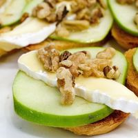 An easy apple-themed appetizer: Top slices of toasted baguette with thin slices of Granny Smith apples and Brie cheese. Drizzle with honey and sprinkle with toasted walnuts.