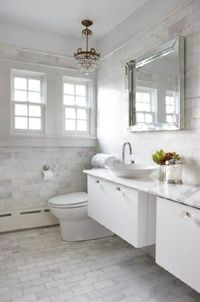 Gorgeous white chic bathroom design with antique brass crystal chandelier, square beveled mirror, overmount round sink, modern floating double vanities with white carrara marble counter tops, glass knobs hardware, white carrara marble subway tiles floors ...