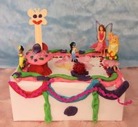 A shoe box covered in white paper makes the perfect canvas to create a play dough cake.