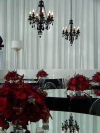 Black chandeliers and mirrored tables with red rose centerpieces