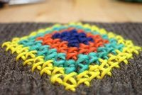 chunky, colorful cross stitch on knitting