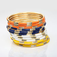 This Gold Bangle Set features bohemian flair set of 3 bracelets alternated in polished gold plating and enamel. Designed in your choice of various colors sets: orange, yellow, blue and white, the Bohemian Stackable Enamel Gold Bangle Set of 3 Bracelets ca...