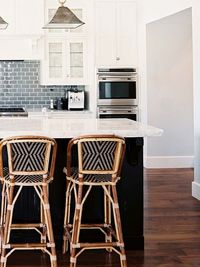 Love the dark island base, and white cabinets, but I would do a Carrera marble backsplash and backless stools